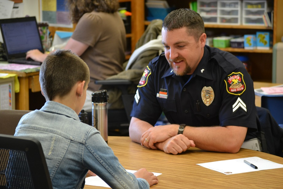 Officer Ryan Phillips listens to a student's writing project at Knollwood Elementary