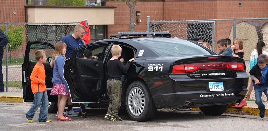 Officer Tim Doyle shows off his patrol car to students at Knollwood Elementary