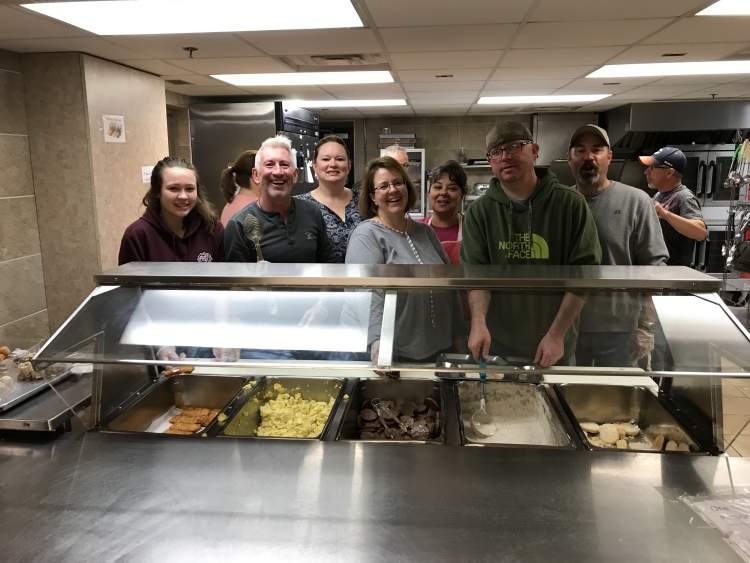 Regional Airport staff prepare and serve meals monthly at the Mission, using the discarded pocket change from travelers for meals and care bags for residents.