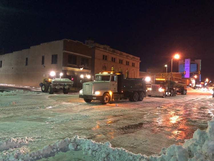 Crews work to remove snow in the downtown core area last month.