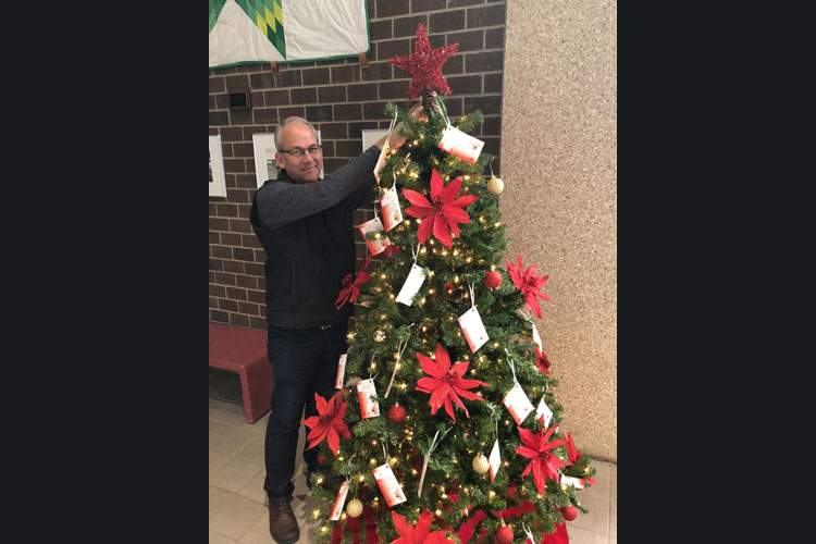 Mayor Steve Allender places a star atop the City Hall Angel Tree.